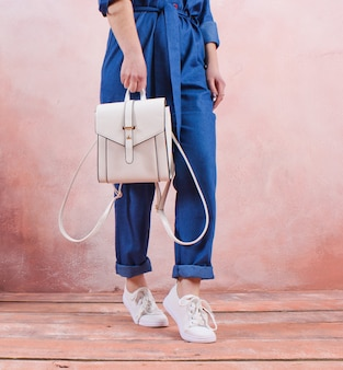 Crop foto einer frau, die einen modischen lederrucksack in ihrer hand gegen den tisch einer lehmwand hält. modekonzept