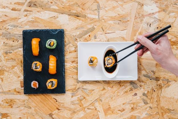 Crop hand eintunken sushi in sojasauce