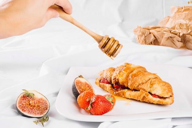 Crop hand gießt honig auf croissant