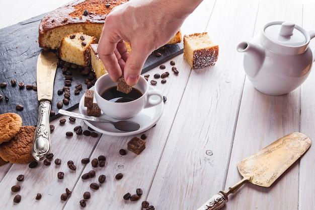 Crop hand zucker zu kaffee hinzufügen
