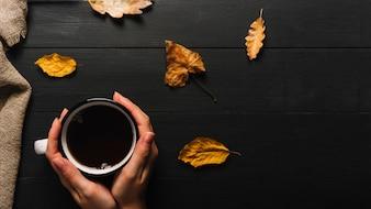 Crop Hände mit Tee in der Nähe von Blättern und Stoff