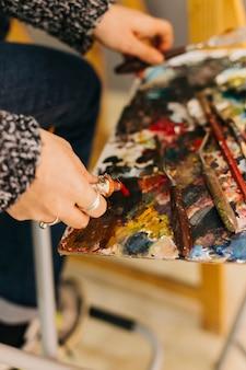 Crop Hände quetschen Farbe auf Palette