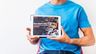 Crop Mann zeigt Tablet mit Netflix Startseite