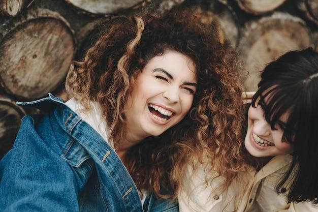 Crop nahaufnahme von frauen in freizeitkleidung mit natürlichem make-up zusammensitzen und entzückend lachen