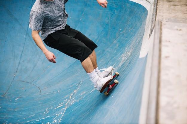 Crop skateboarder reitet auf der rampe