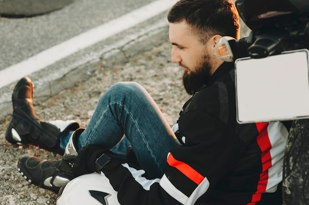 Crop�side-ansicht des unrasierten männlichen fahrers in den jeans, die am abend ruhen, das auf hinterrad des motorrads an der asphaltautobahn lehnt