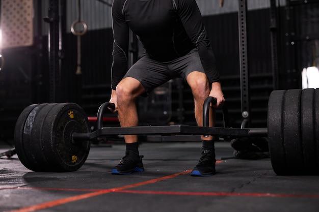 Cropped bodybuilder-typ bereiten sich darauf vor, übungen mit langhantel in einem dunklen, modernen fitnesscenter oder fitnessstudio zu machen. die hand des bodybuilders hebt die langhantel und trainiert allein einen mann in sportlicher kleidung