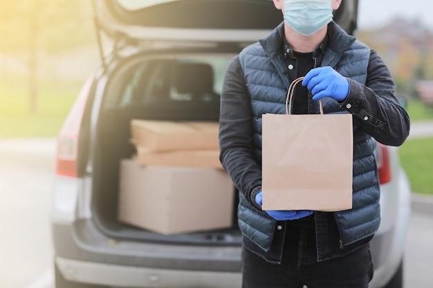 Cropped delivery man in roter kappe, gesichtsmaske und handschuhen halten papiertüte in der nähe des autos im freien