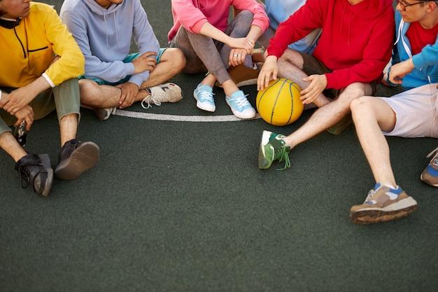 Croppef freundliches team von jungen leuten, die am basketballspielplatz sitzen