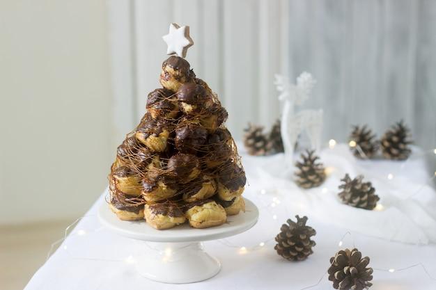 Croquembouche-torte in weihnachts- oder neujahrsdekoration mit tannenzapfengirlande und hirschfigur.