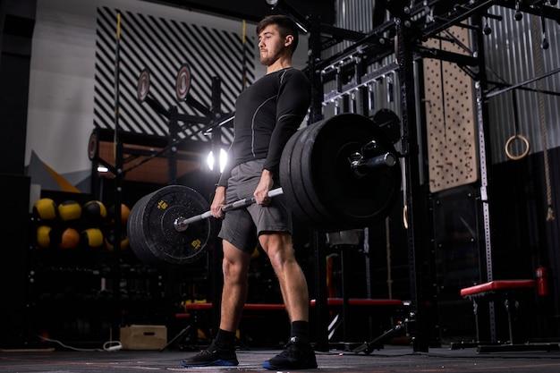 Cross-fit-athlet, der die langhantel im fitnessstudio hebt. mann, der funktionelles training powerlifting-trainingsübungen allein in sportbekleidung übt. gewichtheben, bodybuilding-konzept