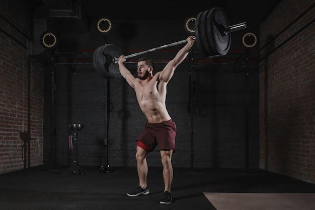 Cross-fit-athlet, der im fitnessstudio die langhantel über den kopf hebt