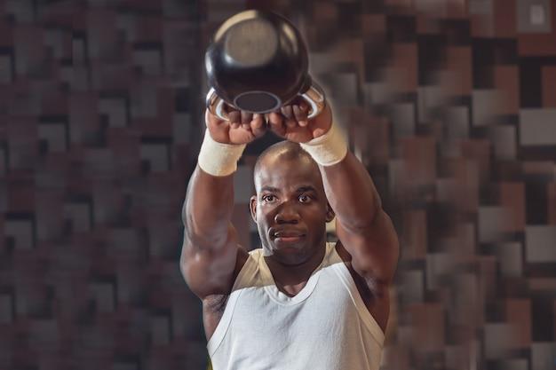 Cross fit training. fitness-mann, der ein krafttraining durch anheben der kettlebell durchführt. junger athlet, der kettlebell schwingt. bodybuilder, der kettlebell anhebt