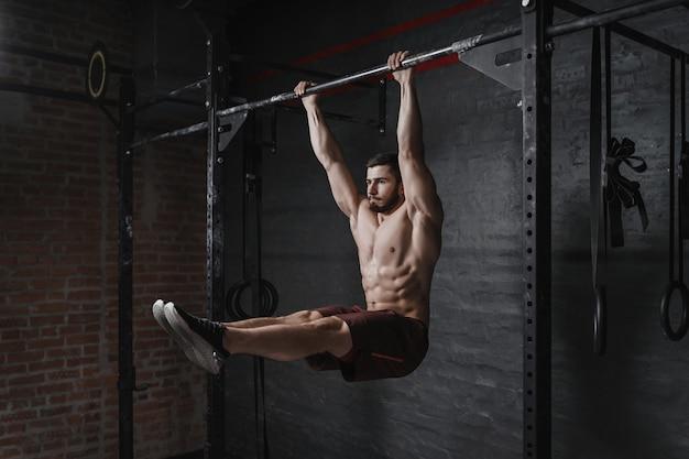 Crossfit-athlet, der im fitnessstudio bauchmuskelübungen an der reckstange macht