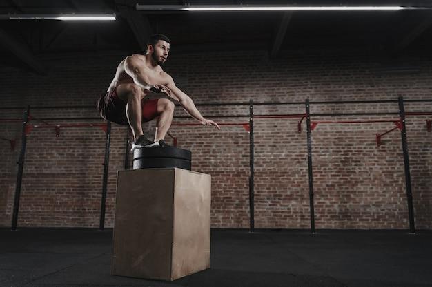 Crossfit-athlet, der im fitnessstudio einen boxsprung durchführt. gut aussehender mann, der funktionelles training macht.