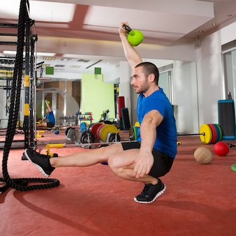Crossfit fitness mann balance kettlebells mit einem bein