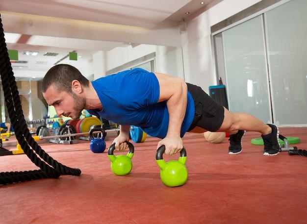 Crossfit-fitnessmann drückt ups kettlebells-liegestütze