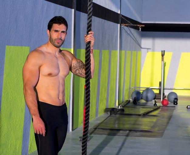 Crossfit mann mit kletterseil entspannt an der turnhalle