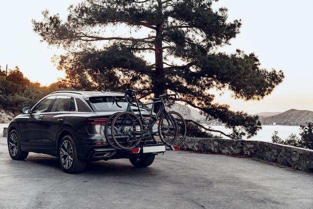 Crossover-auto mit zwei rennrädern, die auf einem auf küstenstraße geparkten gestell geladen werden