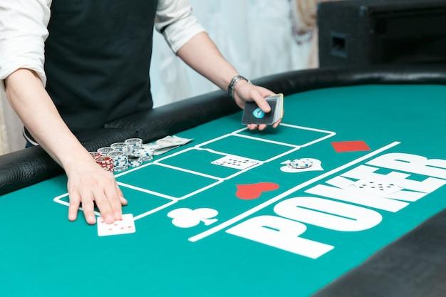 Croupier am pokertisch im casino. chips und karten auf dem tisch.