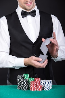 Croupier mit spielenden chips auf der grünen tabelle.