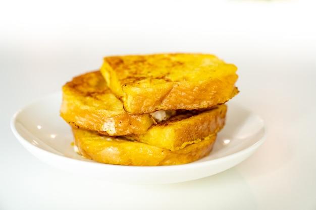 Croutons brot und ei in einem teller auf einem weißen tisch. leckeres, schnelles und einfaches frühstück.