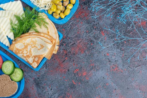 Crpes mit weißem käse und schwarzen und grünen oliven.