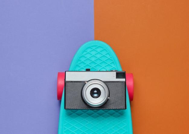 Cruiser board mit retro-kamera auf zweifarbigem papier