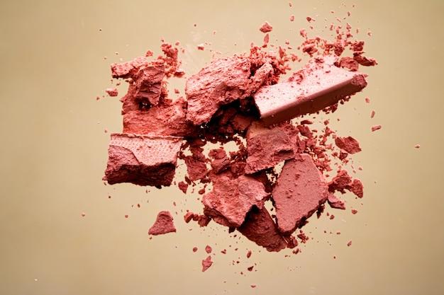 Crushed cosmetics mineral bio lidschatten rouge und kosmetikpuder einzeln auf goldenem hintergrund ...