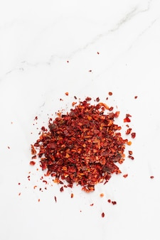 Crushed pimienta roja paprika haufen von oben auf weißem hintergrund. haufen roter pfefferflocken, gemahlener paprika aus rotem chili pfeffer frische und zerkleinerte chili-flocken. koch-, gewürz- und küchenkonzept.