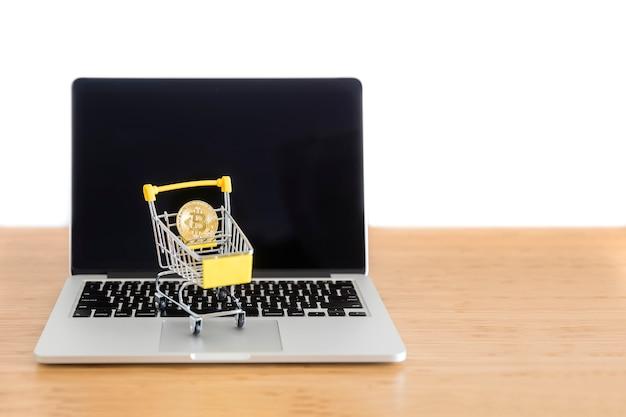 Cryptocurrency-bitcoin in der minisupermarktlaufkatze auf laptop