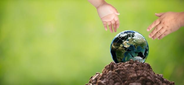 Csr-konzept mit globus, umweltschutzkonzept, hand mit globus vor grünem hintergrund