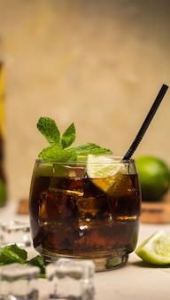Cuba libre-getränk mit tadellosen blättern und kalkstücken.