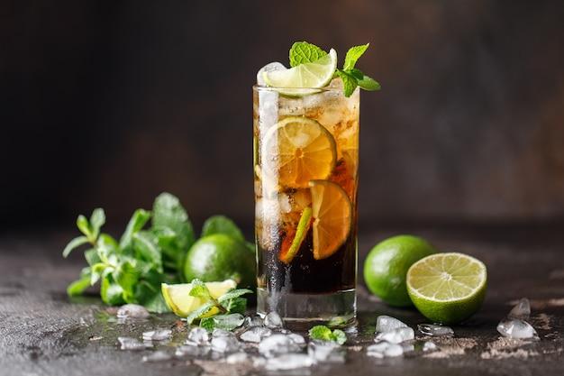 Cuba libre mit braunem rum, cola, minze und limette. cuba libre oder long island eistee cocktail mit starken getränken