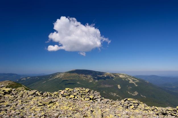 Cumulus-wolke am blauen himmel über der bergkette. sommerlandschaft bei sonnigem wetter. karpaten, ukraine, europa