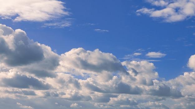 Cumulus-wolken mit blauem himmel an einem sonnigen sommertag. schönes wolkengebilde als naturhintergrundpanorama. wunderbares wetter mit natürlichem tageslicht mit schwebenden weißen wolken, die eine abstrakte form schaffen