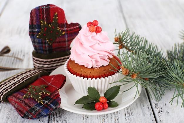 Cup-cake auf untertasse mit weihnachtsdekoration auf farbigem holztisch