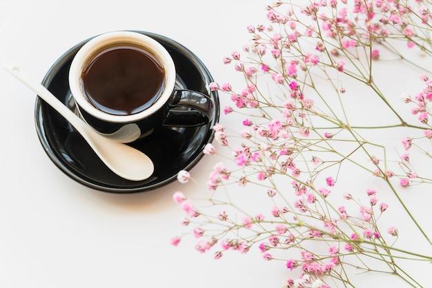 Cup frischer kaffee mit rosa blumen