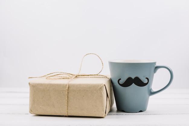 Cup mit dekorativem schnurrbart nahe kasten