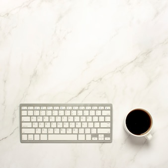 Cup mit kaffee und einer tastatur auf einer marmortabelle. das konzept der arbeit in der nacht, freiberuflich tätig, frühstück. flachgelegt, draufsicht