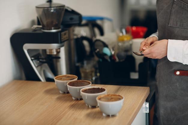Cup-schnupper-frau mit löffel in den händen, die degustations-kaffee-qualitätstest verkosten. kaffee-schröpfen.