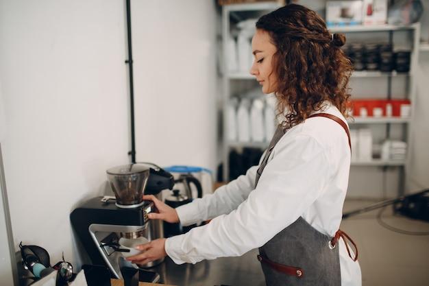 Cup taster girl tasting degustation kaffeequalitätstest. junge frau barista mit kaffeemühle grinder
