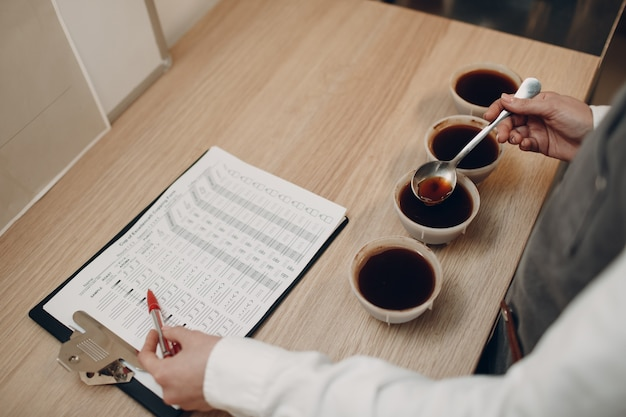 Cup taster girl tasting degustation kaffeequalitätstest. kaffee-schröpfen