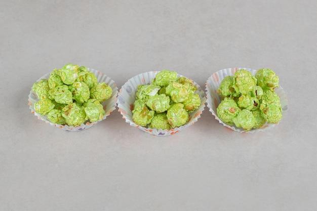 Cupcake-hüllen gefüllt mit aromatisierten popcorn-portionen auf marmortisch.