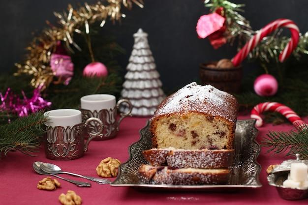 Cupcake mit beeren, nüssen und kandierten früchten, bestreut mit puderzucker auf einer weihnachtskulisse.
