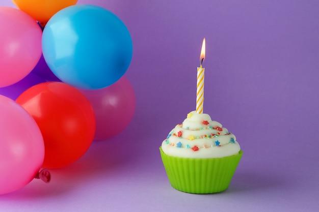 Cupcake mit bunter geburtstagskerze und luftballons