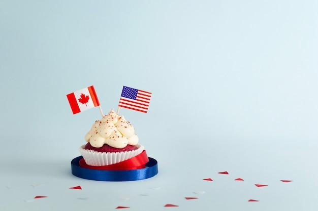 Cupcake mit cremefarbenen kanadischen und amerikanischen flaggen, verziert mit bändern