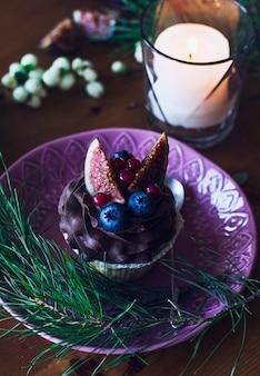 Cupcake mit feigen und beeren auf weihnachtstisch