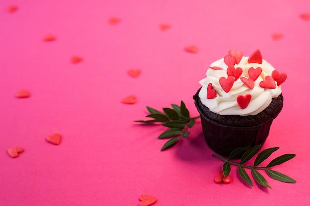 Cupcake mit herzen verziert. liebe. valentinstag konzept. kopierraum, draufsicht.