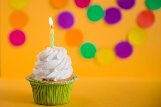 Cupcake mit kerze auf gelbem festpartyhintergrund